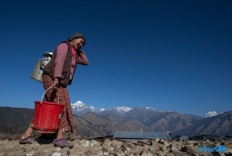 Nepal - Maya Gurung, di 30 anni, trasporta l'acqua nel suo rifugio temporaneo a Gupsi Pakha © UNICEF/UN017117/Shrestha