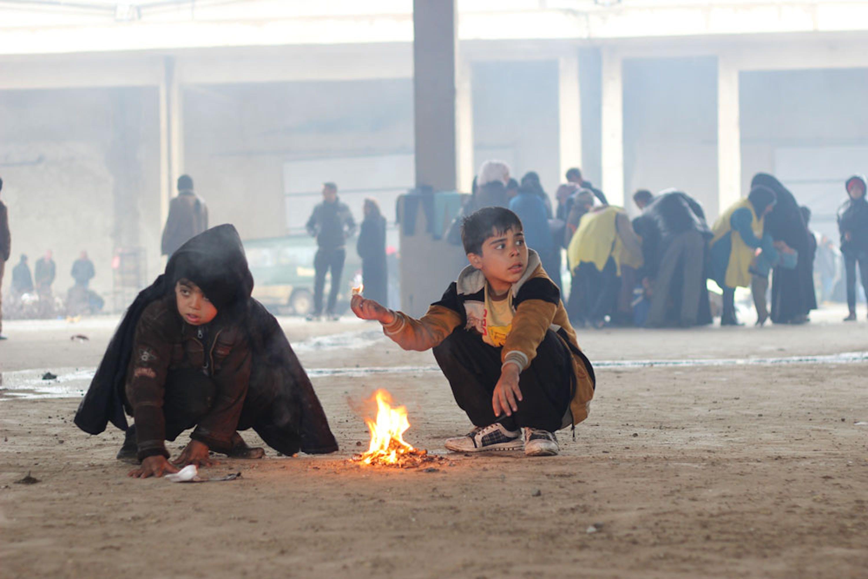 Bambini si scaldano bruciando materiali trovati in giro in questo capannone di Jibreen, sobborgo a est di Aleppo, dove hanno trovato rifugio - ©UNICEF Siria/2016/Al-Issa
