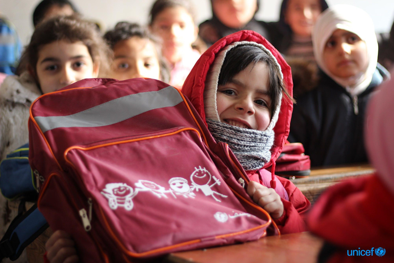 Una bambina sorride con lo zaino scolastico appena ricevuto dall'Unicef © UNICEF/UN051524/Al-Issa