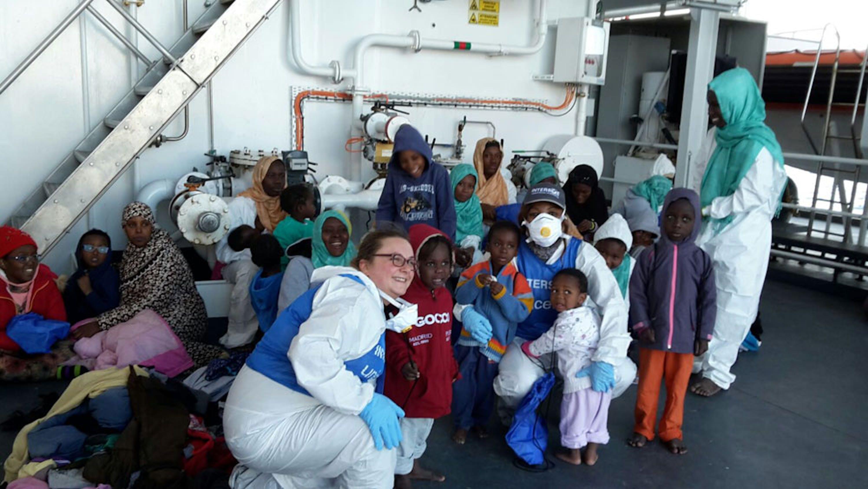 Bambini e mamme con due operatrici di INTERSOS-UNICEF su una nave della Guardia Costiera durante una recente missione di salvataggio nel Mediterraneo