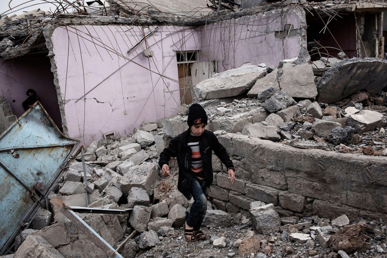 Un bambino fra le macerie di un edificio distrutto da un bombardamento aereo a Mosul Ovest, teatro di violentissimi combattimenti tra forze di sicurezza irachene e ISIS  - ©UNICEF/UN057866/Romenzi