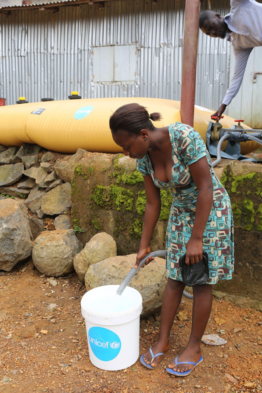 Una donna attinge acqua potabile da una cisterna installata dall'UNICEF a Regent, la cittadina della Sierra Leone maggiormente funestata dalle inondazioni dei giorni scorsi - ©UNICEF/UN076070/James