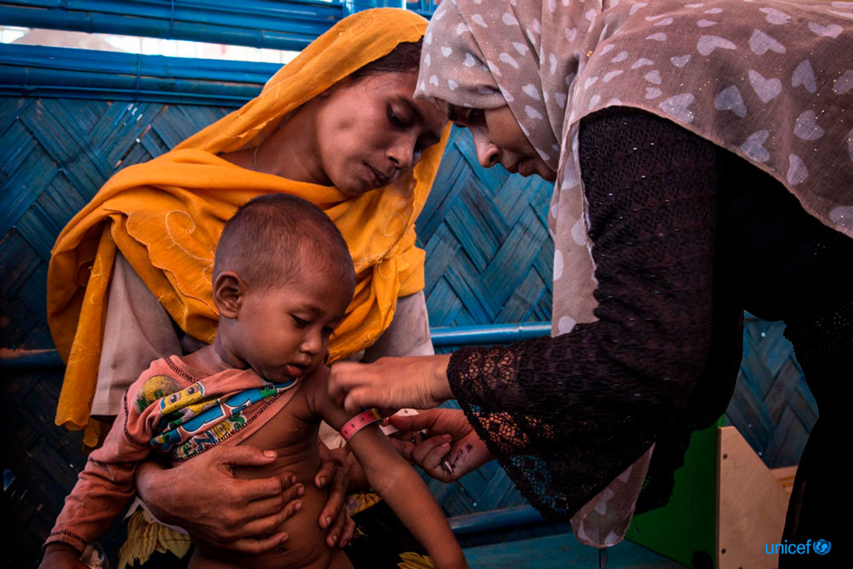 Un operatore sanitario locale  utilizza uno strumento atropometrico per determinare lo stato nutrizionale di questo bambino rohingya © UNICEF/UN0139599/LeMoyne