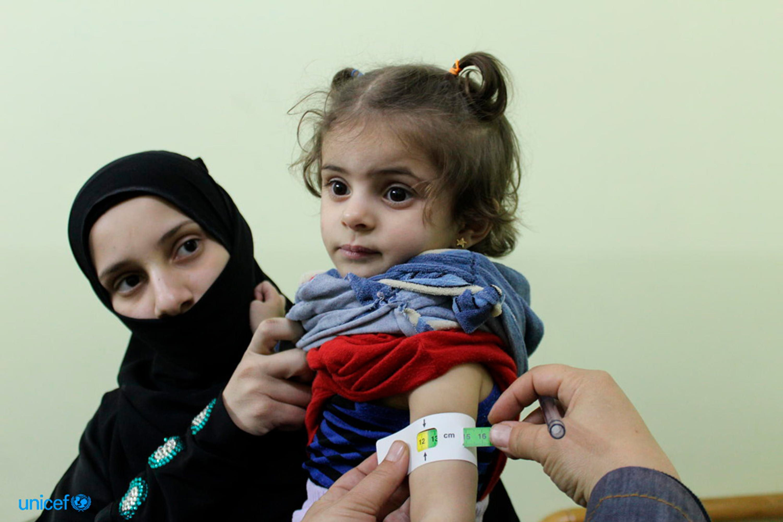 Un operatore sanitario misura lo stato di malnutrizione di una bambina nel corso di una missione umanitaria dell'UNICEF a Kafr Batna, nella zona di Ghouta sotto assedio - ©UNICEF/UN0142210/Tom/OCHA