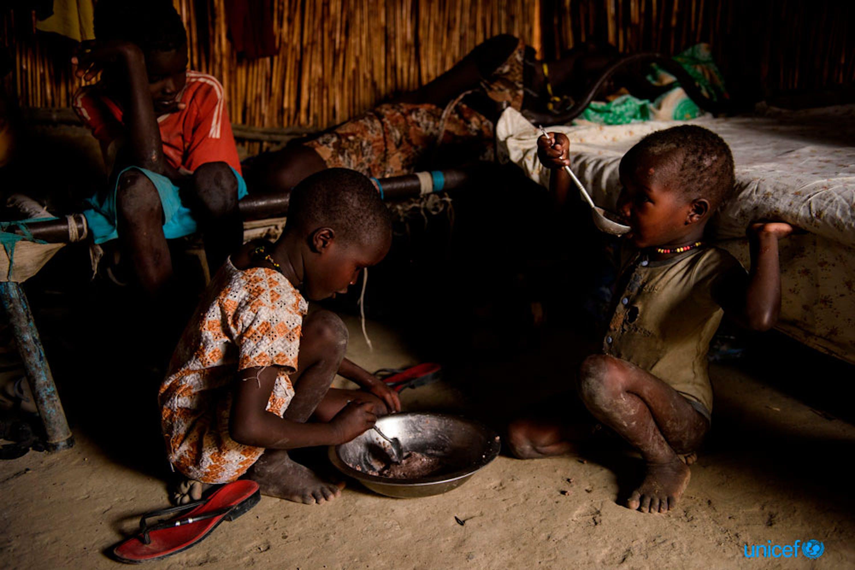 Nyakuma Chol di 7 anni e Nyeyang Chol di 4, mangiano un piatto  di porridge e sorgo nella loro stanza condivisa con altre famiglie sfollate all'interno del sito di protezione dei civili di Bentiu, Sud Sudan - © UNICEF/UN070626/Hatcher-Moore