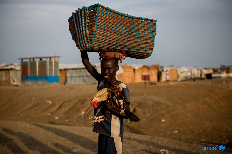 Latjor Mayal di 12 anni porta con se, nel sito di protezione dei civili di Bentiu in Sud Sudan, un cesto di oggetti e un pollo - © UNICEF/UN070627/Hatcher-Moore