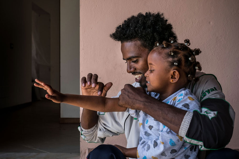 Tesfit, 25 anni, gioca con Bettie, 3 anni, figlia di un suo amico, nel Centro per richiedenti asilo di Mineo (CT). Entrambi provengono dall'Eritrea - ©UNICEF/UN020042/Gilbertson VII Photo