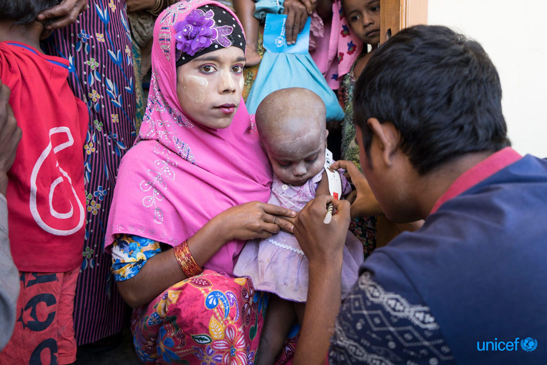 Nel centro nutrizionale del villaggio di Thae Chaung (zona centrale dello stato di Rakhine, in Myanmar) una bambina in braccio alla sua mamma viene monitorata per controllare il suo stato nutrizionale - ©UNICEF/UN0155430/Thame
