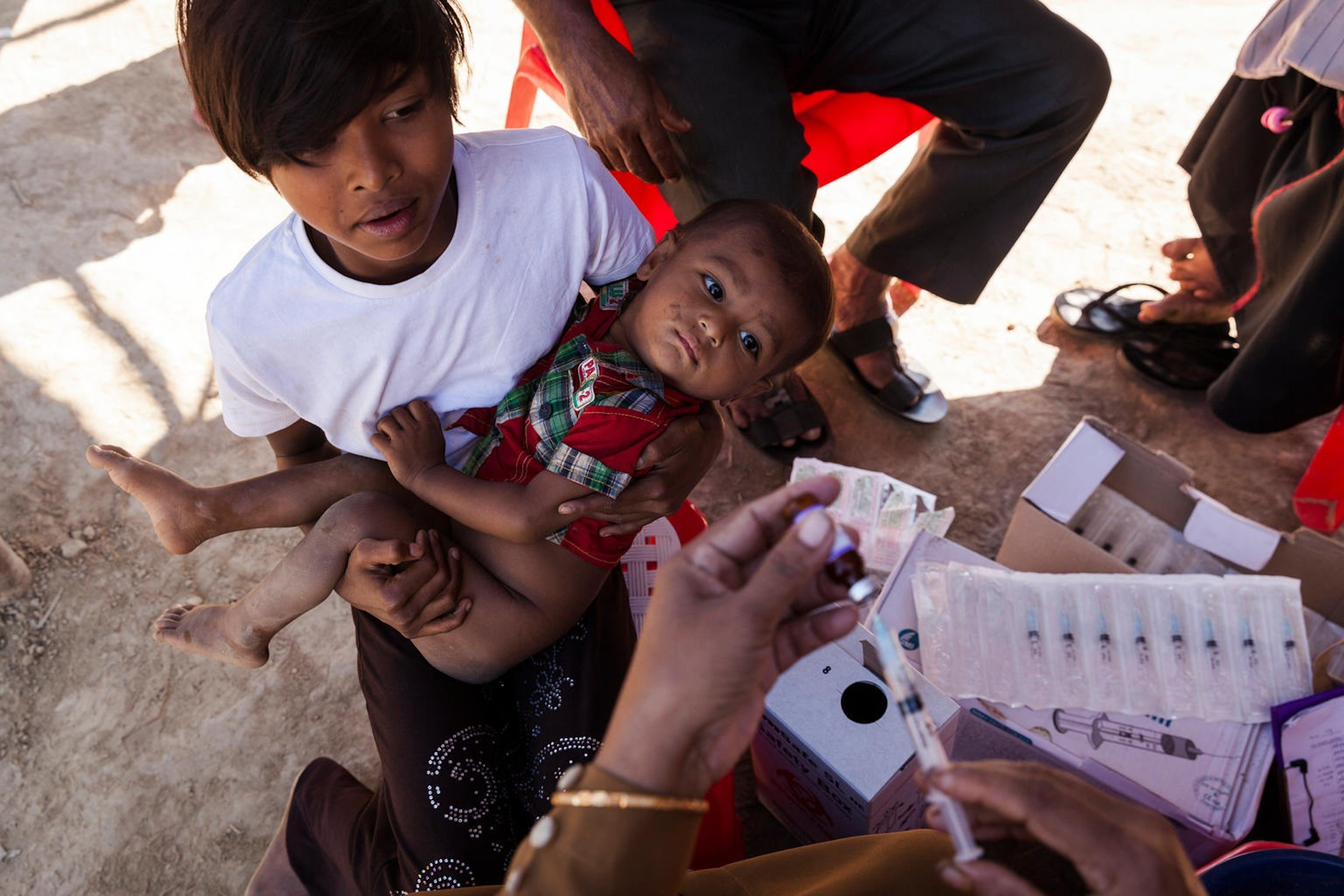 Una giovane mamma porta il suo bambino alla vaccinazione contro il morbillo, in un campo profughi a Cox's Bazar (Bangladesh) -  ©UNICEF/UN0149110/Brown