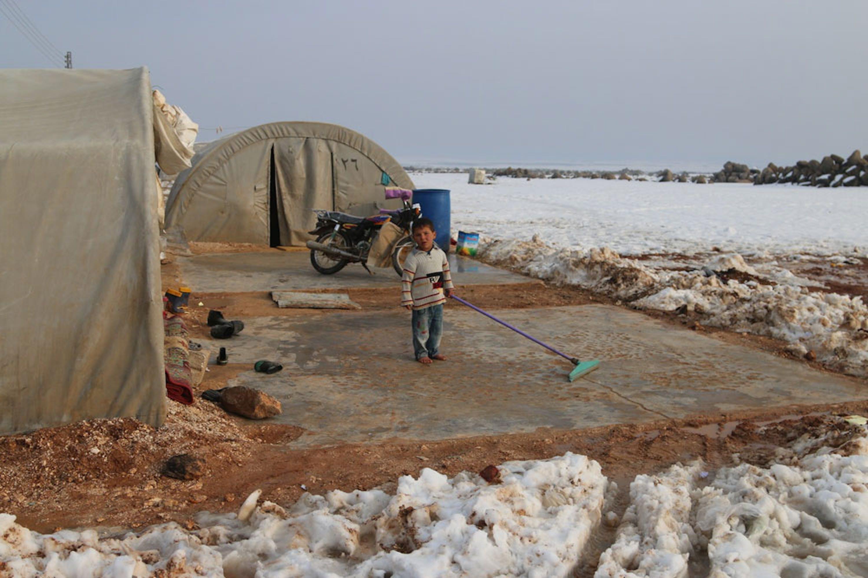 Un bambino spala la neve davanti alla tenda nel campo per sfollati al-Nour, nei dintorni della città siriana di Idlib - ©UNICEF/UN046838/Alwan
