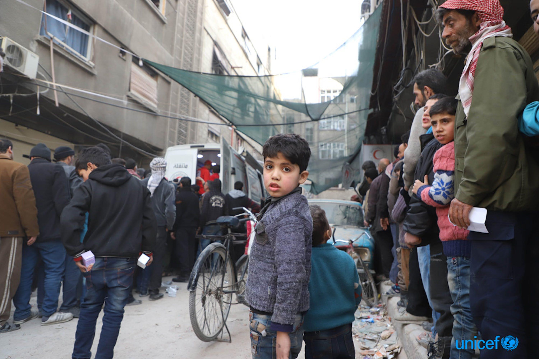 Gli abitanti di Duma, tra cui i bambini, fanno la fila  a un convoglio congiunto UNICEF, ONU e Mezzaluna Rossa siriana di 46 camion, che ha portato aiuti umanitari per 27.500 persone nel  Ghouta orientale, Siria -  © UNICEF/UN0162765/Al-Mohibany