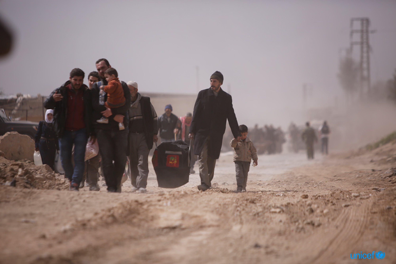 Alcune famiglie camminano verso Hamourieh dove è stato aperto un varco per lasciare la regione del Ghouta orientale, © UNICEF/UN0185410/Sanadiki