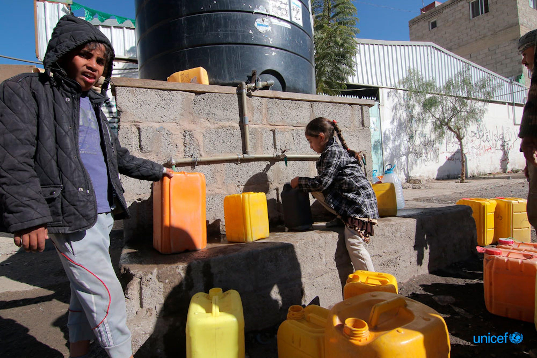 Alcuni bambini riempiono i contenitori di acqua potabile da un serbatoio in una strada di Sana'a,  Yemen  © UNICEF/UN0153966/Alawami