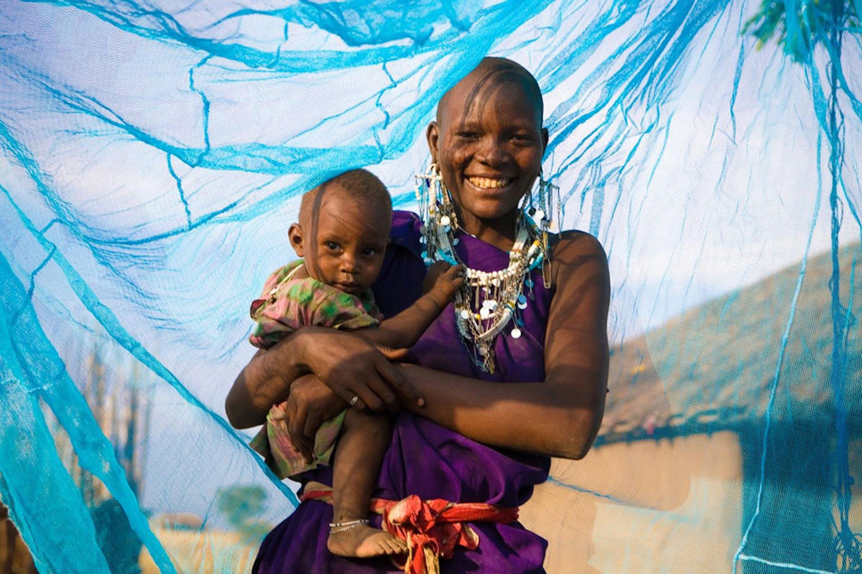 Madre e bambino sotto una zanzariera trattata con insetticida ad Arusha, Tanzania - ©UNICEF/UNI174121/Hallahan