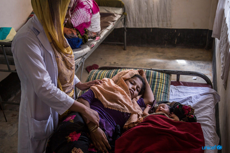 Un'ostetrica con una donna e la sua bambina, nata da soli 3 giorni. nell'ambulatorio del campo di Kutupalong a Cox's Bazar (Bangladesh) - ©UNICEF/UN0139593/LeMoyne