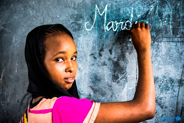 Hawa Oimar, 15 anni, scrive su una lavagna in una classe della sua scuola a Danamadja, Ciad . l'UNICEF fornisce un kit per donne e ragazze, che includono assorbenti igienici,  torcia elettrica e fischietto © UNICEF/UN0122322/Faffin