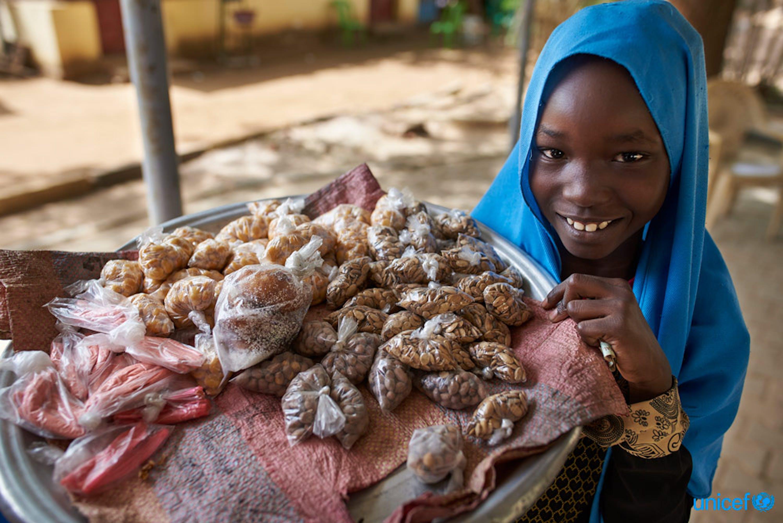 Una bambina vende snacks nella città di Kaduli, Sudan - © UNICEF/UN0211173/Noorani
