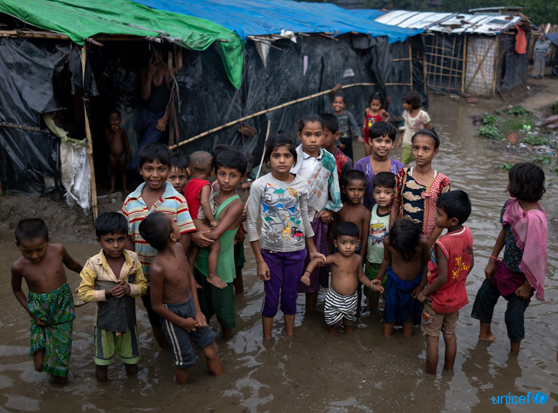 Alcuni bambini rohingya guadano le acque che circondano il loro campo di Cox Bazar dopo una pioggia intensa portata dai monsoni - © UNICEF/UN0213967/Sokol