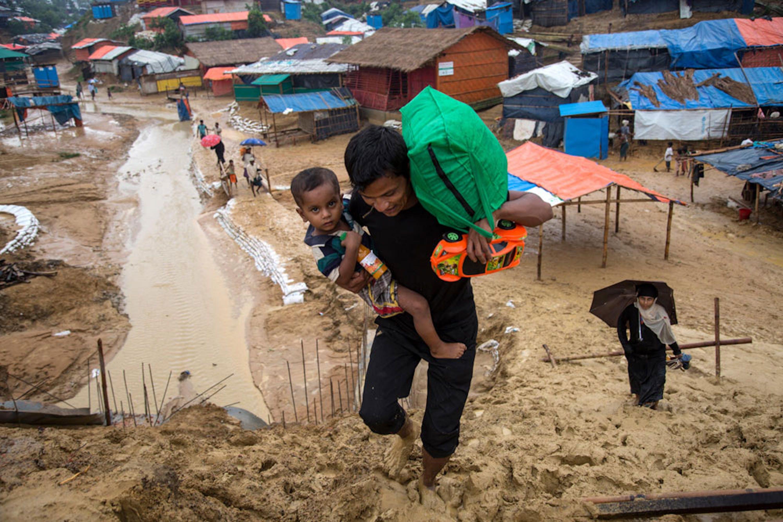 Padre e figlio arrancano nel fango dell'immenso campo profughi di Kutupalong (Bangladesh), il più grande al mondo. Sono circa 900.000 i rifugiati Rohingya attualmente in Bangladesh - ©UNICEF/UN0216991/LeMoyne