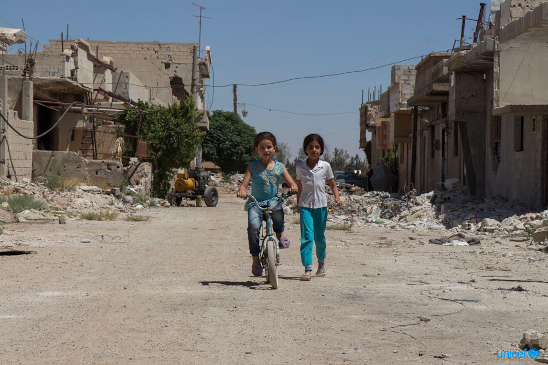 Siria - Sham, una bambina di 10 anni è in sella alla sua bicicletta di fronte a quella che era la sua casa. © UNICEF/UN073942/Nader