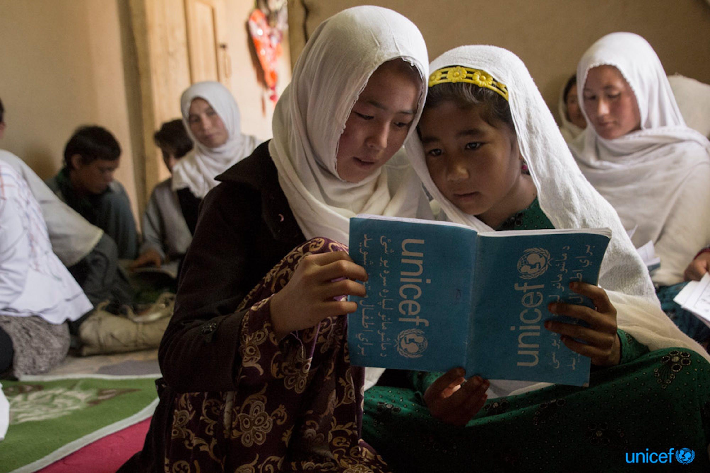 Due ragazze leggono il loro libro di testo durante una lezione nell' Accelerated Learning Centre (ALC) di Sharak e Muhajireen, Afghanistan -  © UNICEF/UN0211158/Rezayee