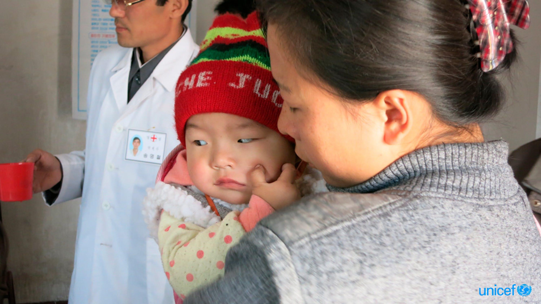 Una mamma e il suo bambino in attesa del loro turno per ricevere il supplemento di Vitamina A e Vermifughi - © UNICEF/UNI180565/Basurmanova