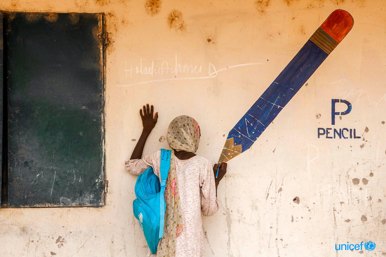 Aisha, 13 anni, finge di disegnare sulla punta di una matita dipinta su un murale in un campo per sfollati nello stato di Adamawa, in Nigeria. © UNICEF/UNI181410/Esiebo