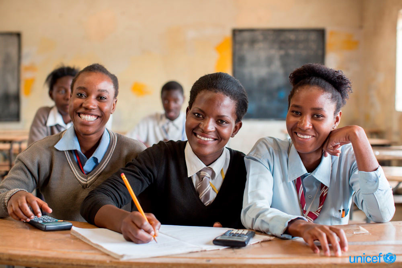 Tre adolescenti, tra cui una che prende appunti, sorridono durante una lezione, nella Kamulanga Secondary School di Lusaka, la capitale - © UNICEF/UN0145551/Schermbrucker