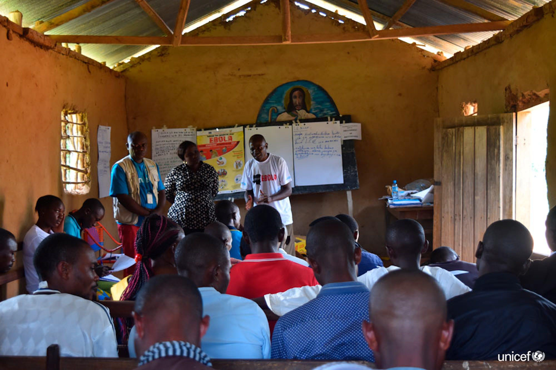 Congo, un sopravvissuto all'Ebola e un operatore dell'Unicef esortano i membri di una comunità locale nel Nord Kivu a condividere le informazioni sui sintomi dell'epidemia - © UNICEF/UN0231606/Herrmann