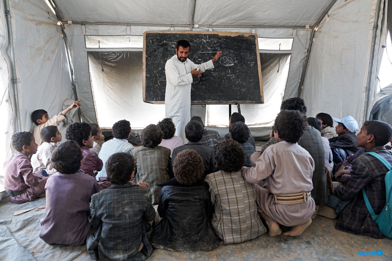 Un gruppo di studenti ascoltano il loro insegnante durante una lezione tenuta in una tenda dell'UNICEF, dopo che la loro scuola Aal Oka B è stata distrutta dai bombardamenti. © UNICEF/UN073956/Clarke for UNOCHA