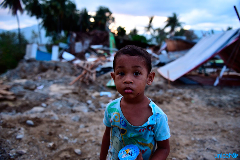 Muhamad Nafi, di 2 anni, è tra le rovine della sua casa distrutta dal recente tsunami nel villaggio di Lolu,  a Palu, nelle Sulawesi centrale - © UNICEF/UN0245434/Wilander