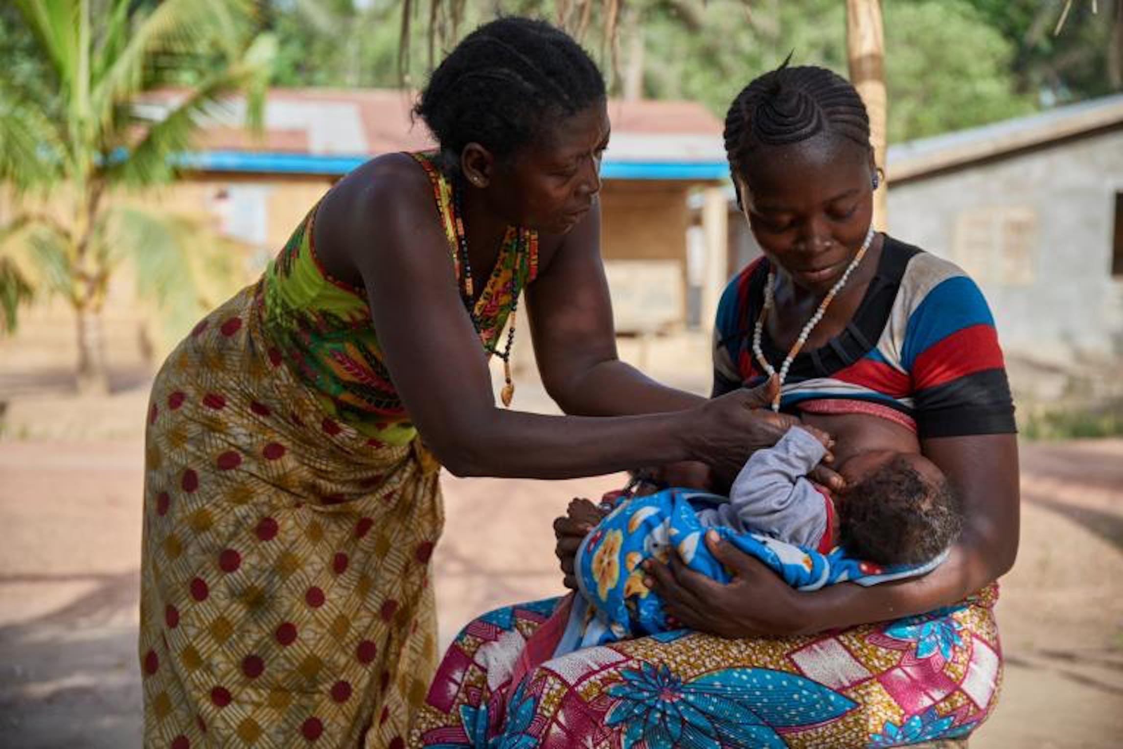 Zainab Kamara, sostenuta da sua madre, allatta uno dei suoi due  gemelli di 3 mesi - © UNICEF/UN065254/