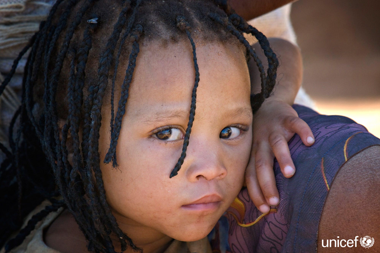 Namibia - Una bambina indigena del gruppo etnico San siede con sua madre fuori dalla loro casa nell'insediamento di  Epako, un sobborgo della città di Gobabis nella regione di Omaheke, vicino al confine con il Botswana - © UNICEF/UNI99397/Isaac