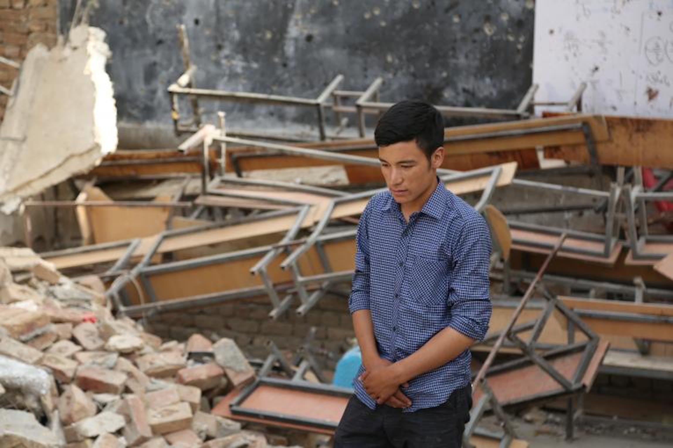 Un ragazzo in una scuola distrutta dai combattimenti - © UNICEF/Afghanistan