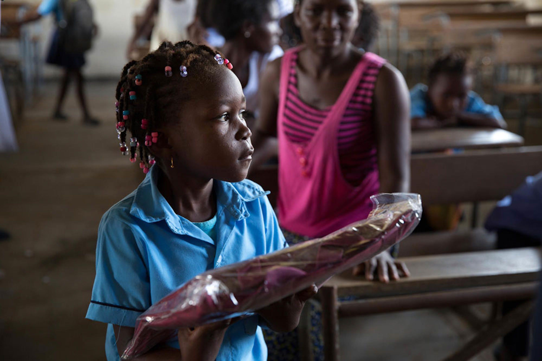 Sonia (6 anni) riceve un kit didattico nella scuola elementare