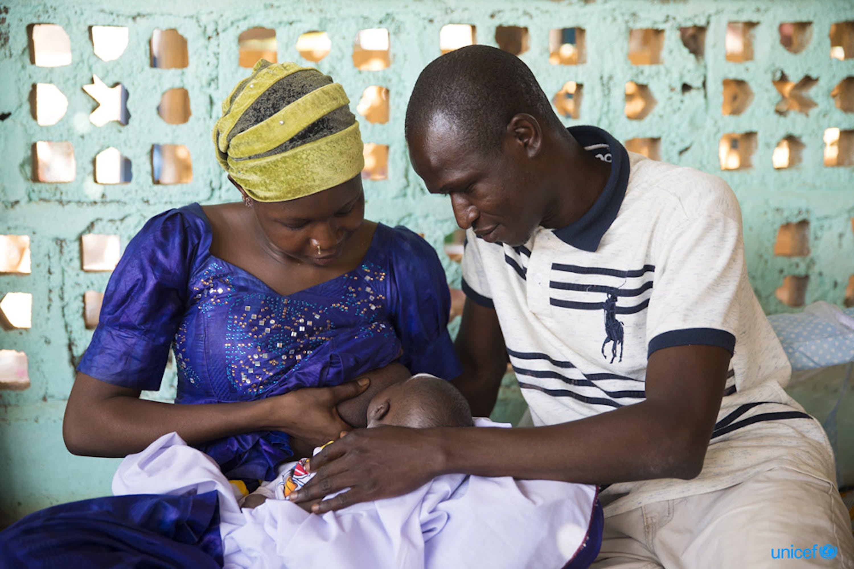 in Mali, Hawa Diawara  allatta il suo bambino di 24 giorni, Youssouf Sanogo, accanto al marito sorridente - © UNICEF/UN0205719/Njiokiktjien VII Photo