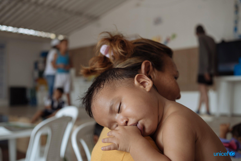In Colombia, un bambino riposa sulla spalla di sua madre presso il Friendly Space (CATM) a Cucuta, dove l'UNICEF fornisce attività di apprendimento per i bambini migranti e i genitori del Venezuela. © UNICEF/UN0304586/Arcos
