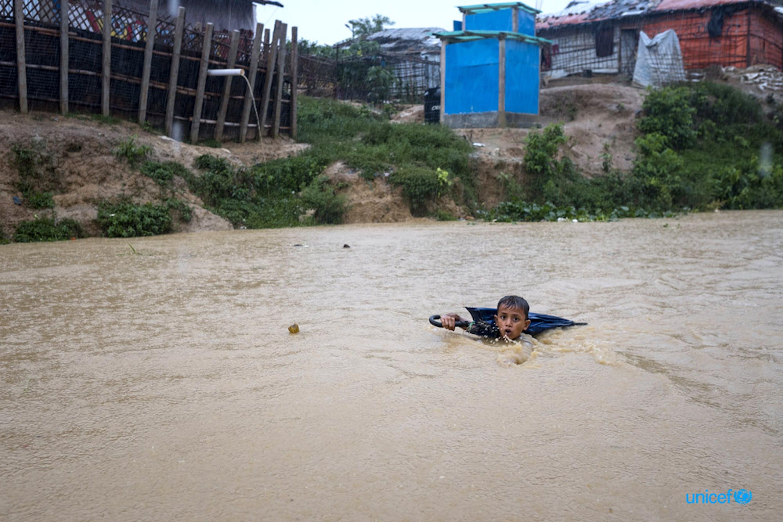 Bangladesh, un giovane ragazzo naviga in un fiume gonfio dai giorni di pioggia dei monsoni - © UNICEF/UN0326875/Nybo