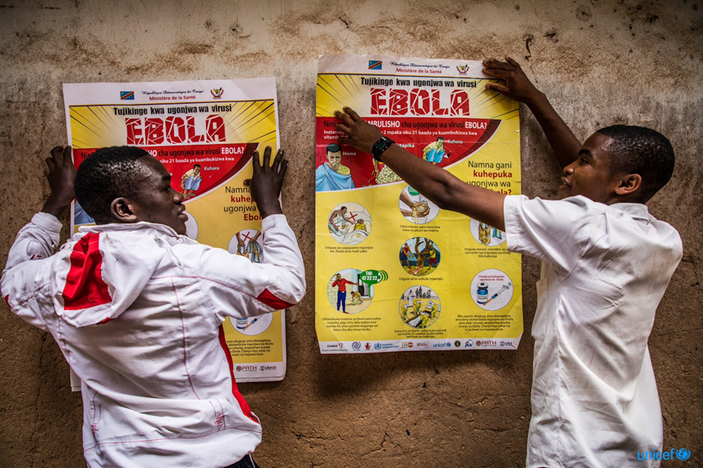 Congo. due studenti affissano alla parete della loro scuola un poster che descrive la sensibilizzazione all'ebola  © UNICEF/UN0311511/Tremeau