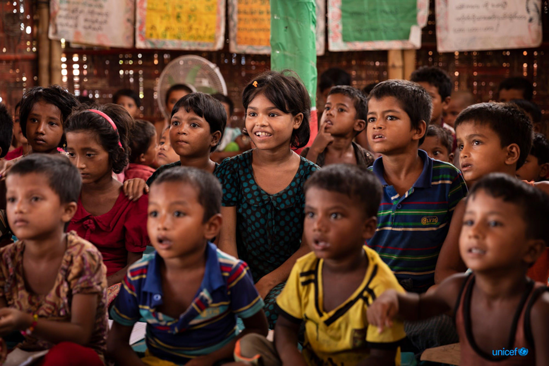Un gruppo di bambini recitano la lezione quotidiana in uno spazio di apprendimento sostenuto dall'UNICEF nel campo di Kutupalong-Balukhali, Cox's Bazar, Bangladesh © UNICEF/UN0326961/Brown