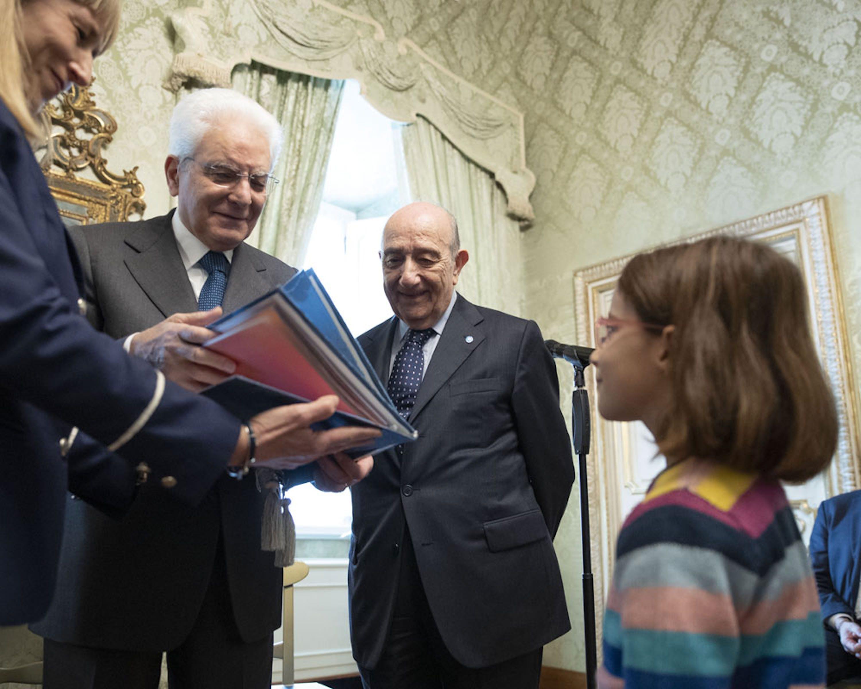 Il presidente Mattarella riceve una copia speciale della Convenzione sui Diritti dell'Infanzia. Accanto a lui il presidente dell'UNICEF Italia Francesco Samengo e la piccola Carolina - ©Quirinale