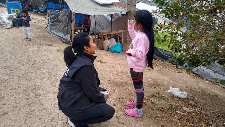 La vicerappresentante dell'UNICEF in Messico Pressia Arifin-Cabo parla con una bambina nell'accampamento di Matamoros, al confine tra Messico e USA - © UNICEF/UNI285132_Vergara Toache
