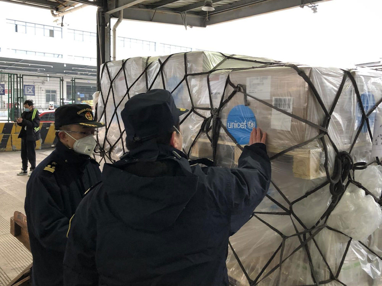 Addetti dell'aeroporto internazionale di Shangai (Cina) ispezionano il carico giunto dalla UNICEF Supply Division di Copenaghen con migliaia di tute protettive, mascherine e altri articoli per il contrasto dell'epidemia di SARS-CoV-2 - © UNICEF/UNI284471