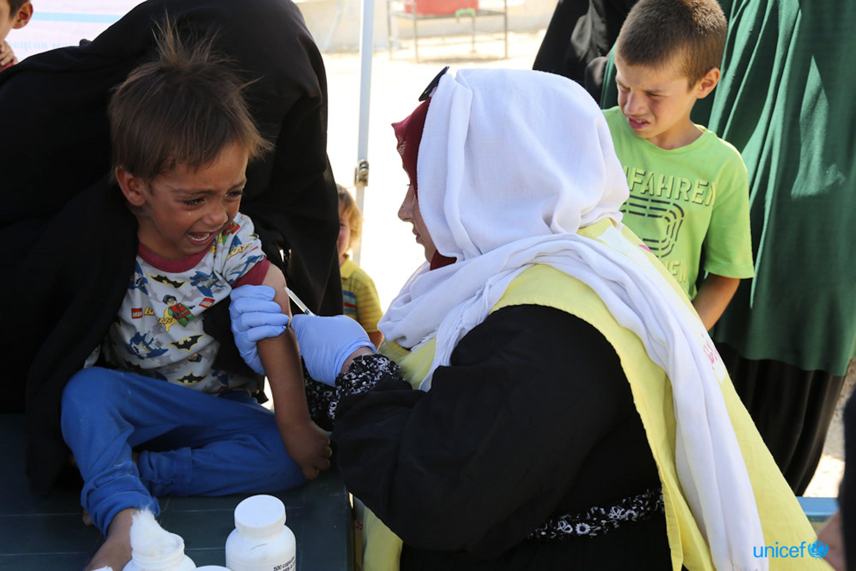 Un'operatrice di un team sanitario mobile dell'UNICEF somministra una vaccinazione a una bambina nel campo di Al-Hol, nel nord-est della Siria - ©UNICEF/UN0327927/Hawas