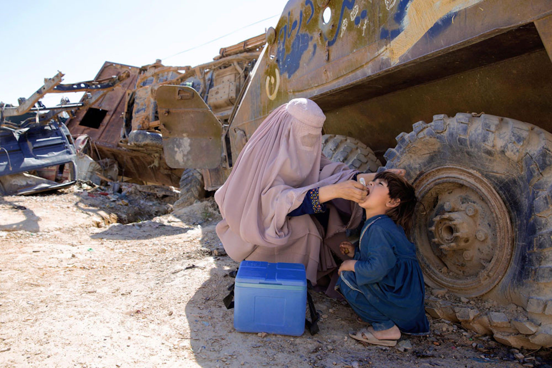 Un bambino riceve una vaccinazione antipolio all'ombra di un carrarmato, in Afghanistan - ©UNICEF/UN0202762/Hibbert