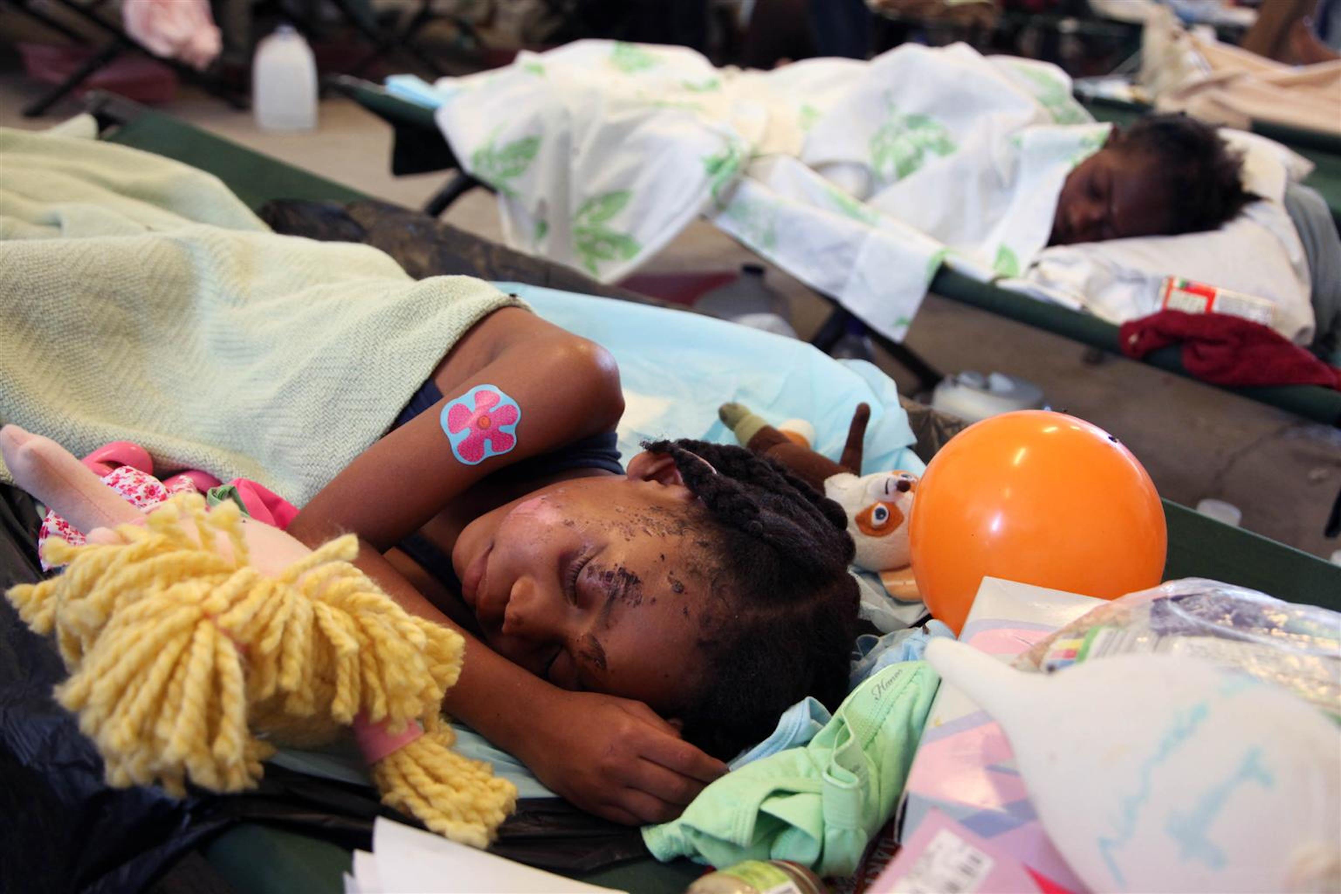 Questa bambina ferita è rimasta isolata dai genitori. Mentre procedono le ricerche è ospite presso un ospedale da campo in attesa di essere inserita in una casa-famiglia di Port-au-Prince