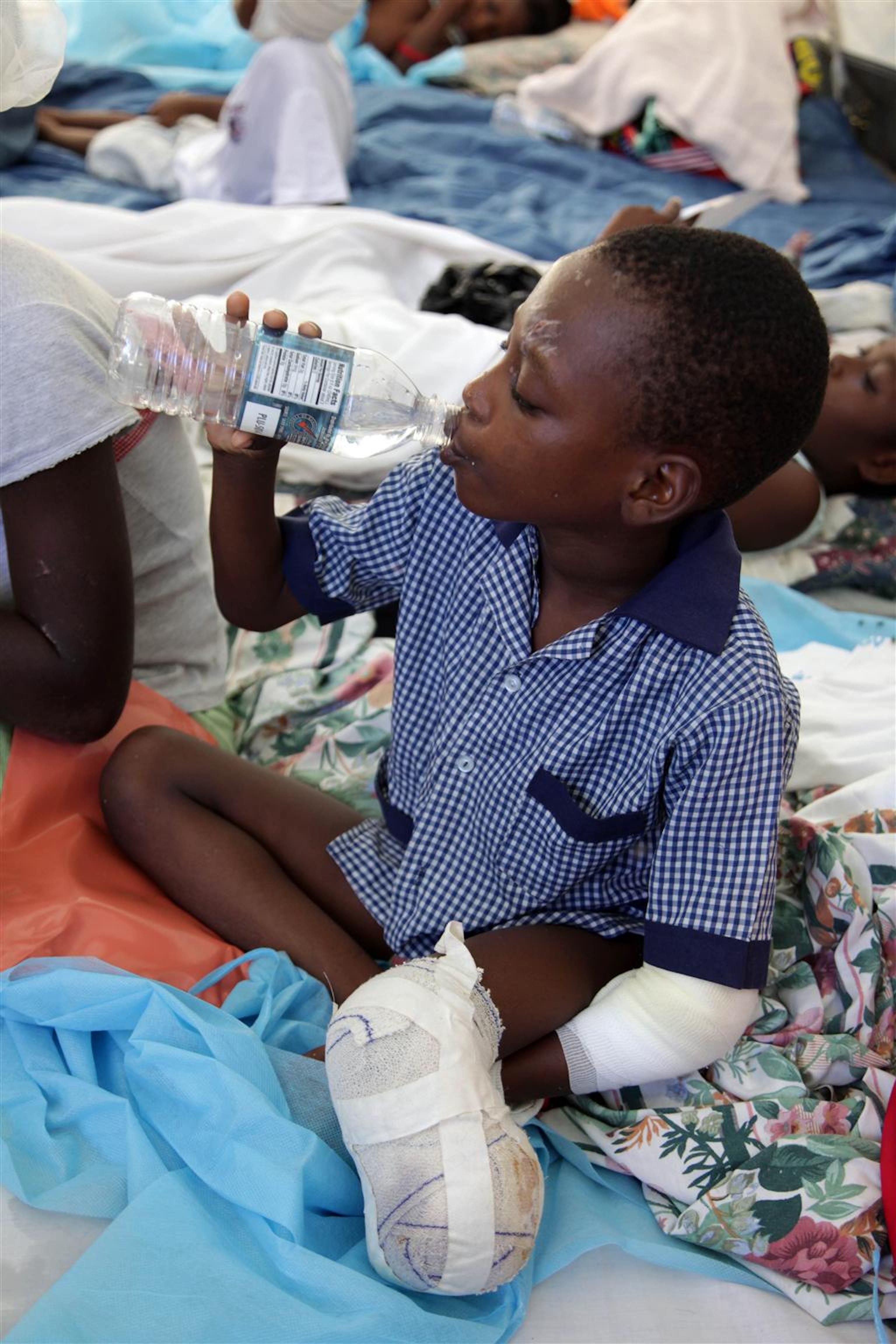 Un bambino che ha subito un'amputazione alla gamba sinistra beve in una tenda dove è stato allestito il reparto pediatrico dell'Ospedale Generale di Port-au-Prince. L'UNICEF rifornisce acqua in bottiglia a quasi tutti gli ospedali della capitale haitiana