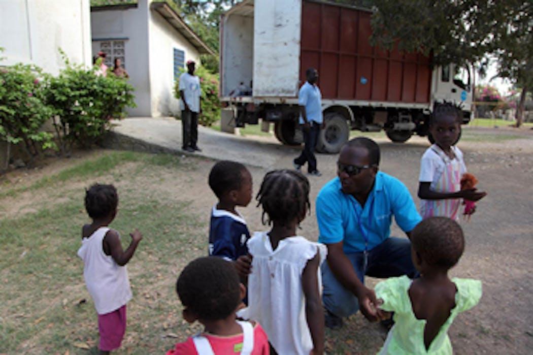 Un operatore dell'UNICEF parla con alcuni bambini dell'orfanotrofio di Tabarre, quartiere della capitale Port-au-Prince