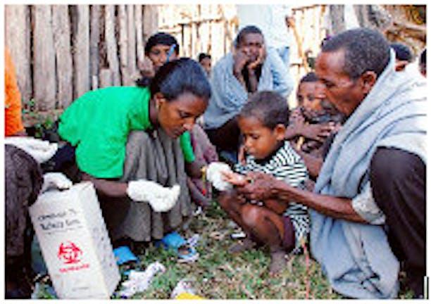 Un operatore sanitario esegue su un bambino il test per la malaria con un kit di diagnosi rapida