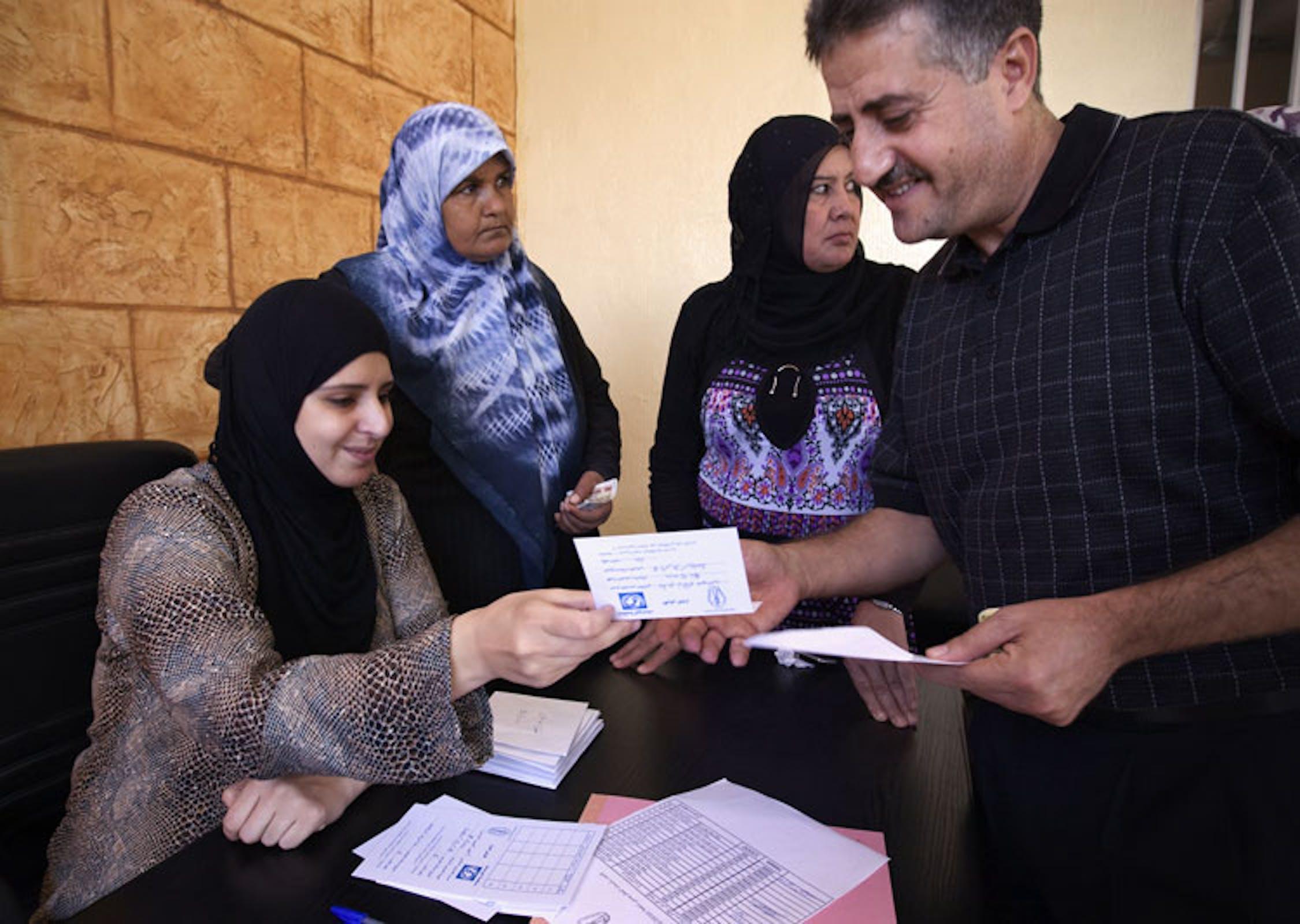 Un uomo riceve dei soldi in prestito da un gruppo di donne che gestiscono il programma di microcredito finanziato dall'UNICEF. ©Ada Lombardi/UNICEF Italia/2010